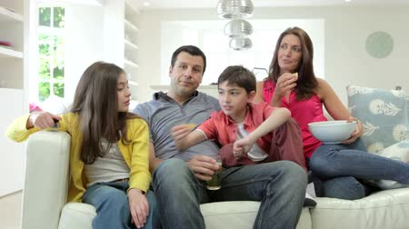 snack : Hispanic Family Sitting On Sofa Watching TV Together Stock Footage