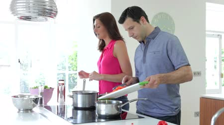 culinária : Hispanic Couple Cooking Meal At Home