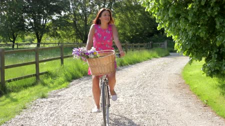 kırsal : Attractive Woman Riding Bike Along Country Lane Stok Video