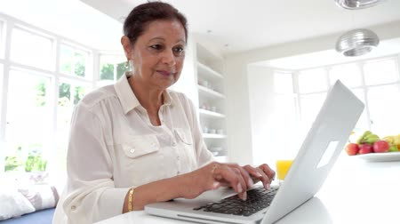 hint : Senior Indian Woman Using Laptop Computer At Home