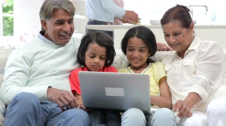 país : Multi-Generation Indian Family With Laptop Sitting On Sofa