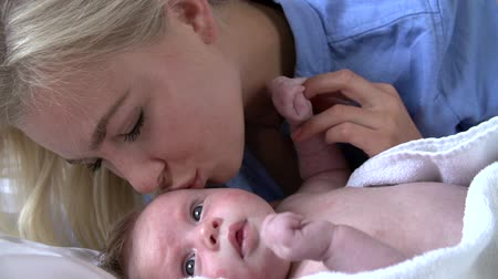 newborn baby : Slow Motion Sequence Of Mother Kissing Baby Daughter In Bed
