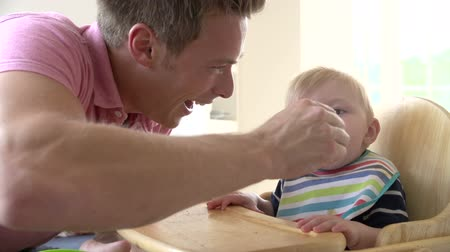 feed on : Slow Motion Shot Of Father Feeding Baby Boy In High Chair Stock Footage