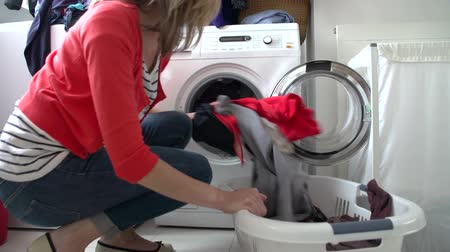 roupas : Woman Loading Clothes Into Washing Machine