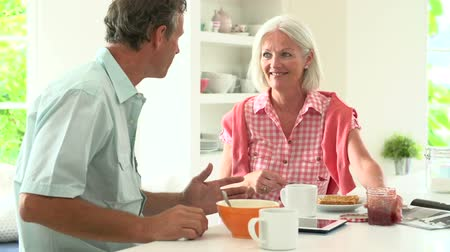 elliler : Middle Aged Couple Having Breakfast Together In Kitchen