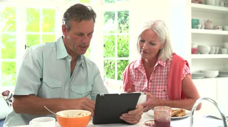 časopis : Middle Aged Couple Looking At Digital Tablet Over Breakfast