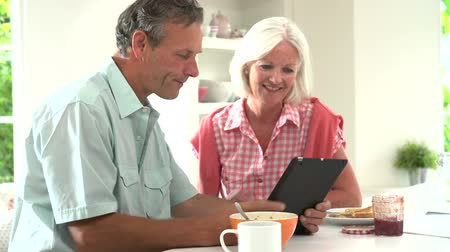 elliler : Middle Aged Couple Looking At Digital Tablet Over Breakfast