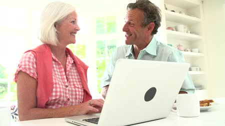 párosít : Middle Aged Couple Looking At Laptop Over Breakfast  Stock mozgókép