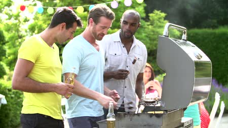man eating : Group Of Men Cooking On Barbeque At Home
