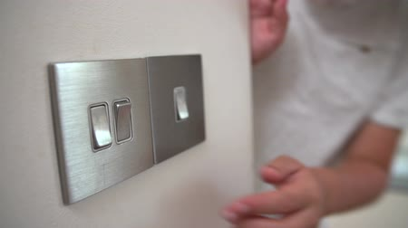 comutar : Slow Motion Sequence Of Boy Turning Off Light Switch