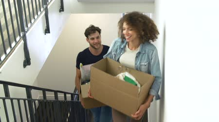 guy home : Couple Moving Into New Home Carrying Box Upstairs