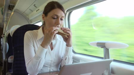 öltöny : Female Commuter On Train Using Laptop Whilst Eating Sandwich
