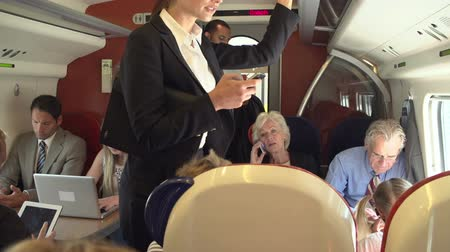 oblek : Businesswoman Using Mobile Phone On Busy Commuter Train