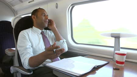 black tea : Businessman Commuting To Work On Train Using Mobile Phone Stock Footage