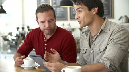 içme : Two Male Friends In Coffee Shop Looking At Digital Tablet