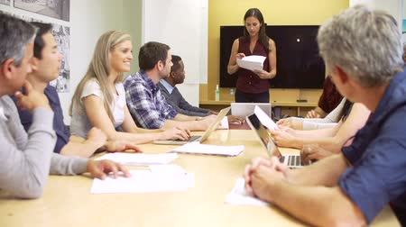 boss : Female Boss Addressing Meeting Around Boardroom Table