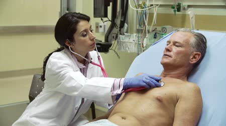 estetoscópio : Doctor Examining Mature Male Patient In Hospital Bed