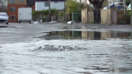 escaping : Flood Water Escaping From Drain Cover In Slow Motion Stock Footage