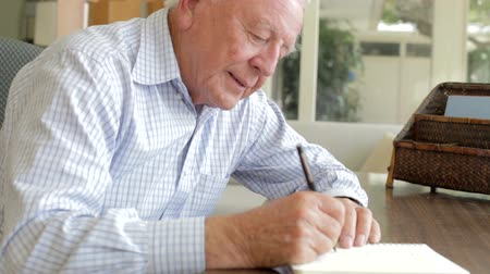 Senior Man Writing Memoirs In Book Sitting At Desk Stok Video