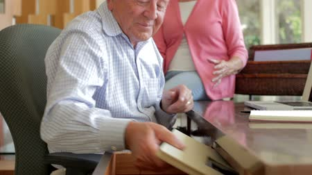 çerçeveler : Senior Couple Looking At Picture In Frame And Photo Album