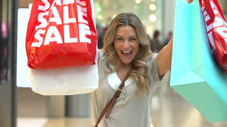 покупка товаров : Slow Motion Sequence Of Woman In Mall Holding Up Sale Bags