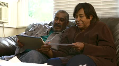 bankjegyek : Worried Senior Couple Sitting On Sofa Looking At Bills