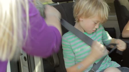 vacation : Mother Making Sure Children Are Safe In Back Seat Of Car