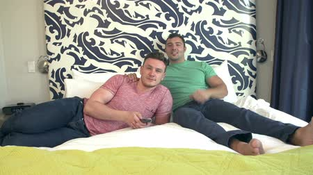 гей : Male Couple Relaxing In Hotel Room Watching Television