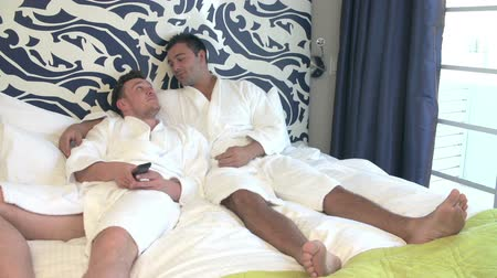 гей : Male Couple In Robes Watching Television In Hotel Room