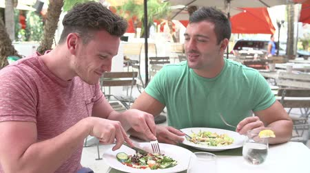 lunch : Male Couple Enjoying Lunch In Outdoor Restaurant Stock Footage