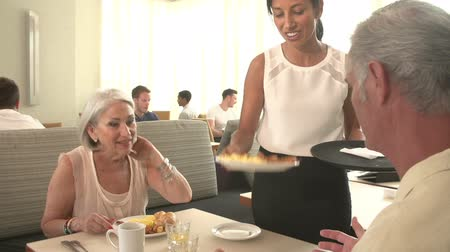 elliler : Waitress Serving Senior Couple Breakfast In Hotel Restaurant Stok Video