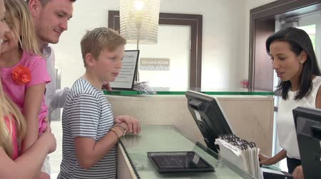 reception : Family Checking In At Hotel Reception Using Digital Tablet