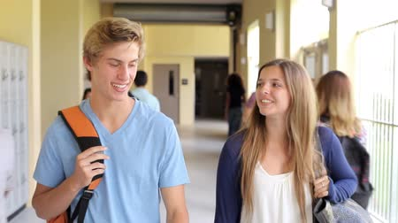 High School Student Couple Walking Along Hallway Stok Video