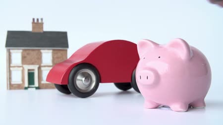 bringing home the bacon : Putting Coin Into Piggy Bank With Model House And Car Behind Stock Footage
