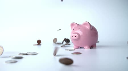 bringing home the bacon : Coins Falling Around Piggy Bank In Slow Motion