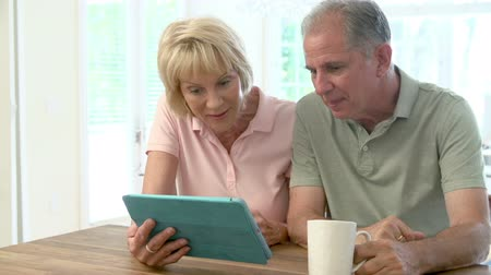 elliler : Senior Couple Making Online Purchase Using Digital Tablet Stok Video
