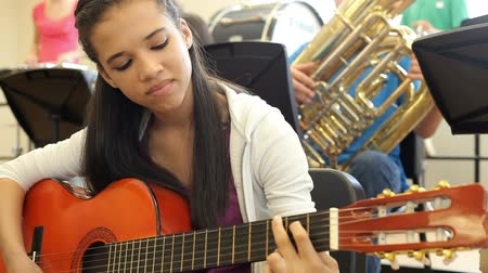 playing band : Female Pupil Playing Guitar In High School Orchestra