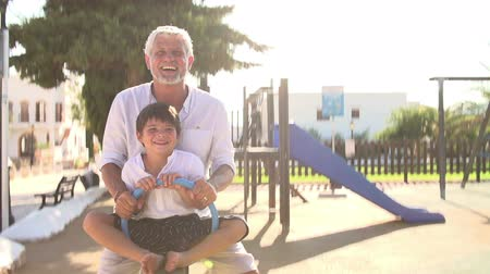 grandchild : Grandfather And Grandson On Seesaw In Playground