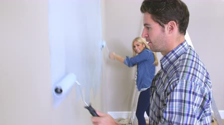 malarstwo : Couple Decorating Room Using Paint Rollers On Wall Wideo