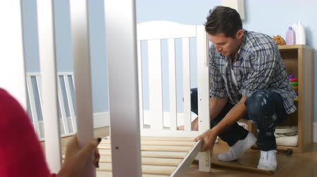 toolbox : Couple With Pregnant Wife Assembling Cot In Nursery