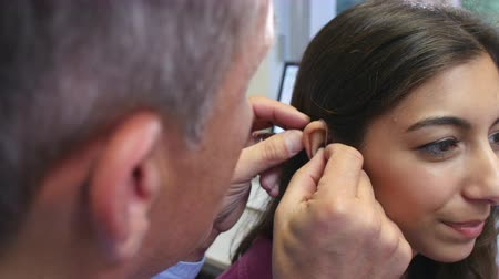 sluch : Doctor Fitting Female Patient With Hearing Aid Dostupné videozáznamy