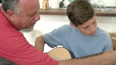 helping : Grandfather Teaching Grandson To Play Guitar