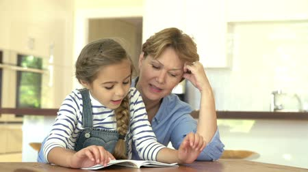 бабушка : Grandmother Helping Granddaughter With Reading At Home
