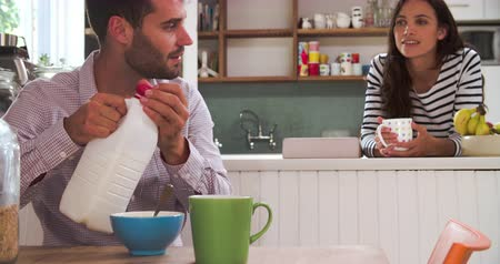 onto : Young Couple Eating Breakfast In Kitchen Together