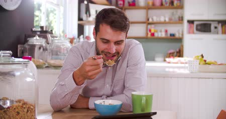 man eating : Young Man Eating Breakfast Whilst Using Digital Tablet