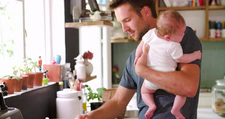 Father Cooking Meal Whilst Holding Baby In Kitchen