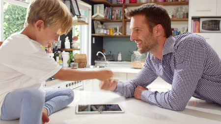 mutfak : Father And Son Playing Game On Digital Tablet In Kitchen Stok Video