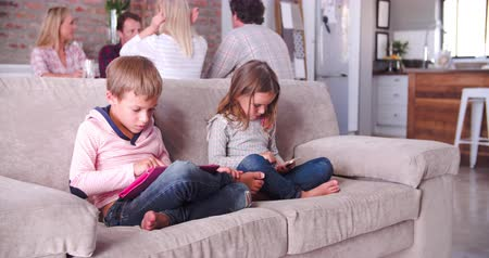 país : Children Use Digital Devices As Parents Talk In Background