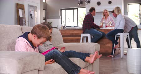 gibi : Children Use Digital Devices As Parents Drink Wine Stok Video