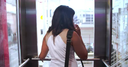 лифт : Businesswoman Riding Elevator And Talking On Mobile Phone Стоковые видеозаписи